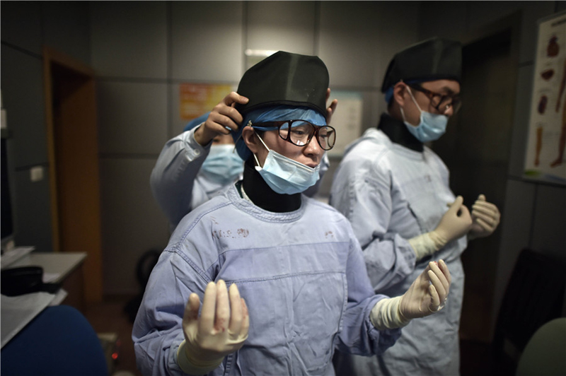 06e0322d4f6 Liu Ya takes off surgical mask to catch a breath after operating an  interventional radiology surgery.