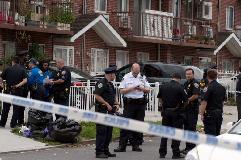 Police gather outside a daycare centre at a private home after a stabbing in the Queens borough of New