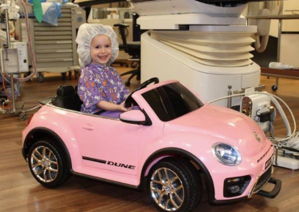 Caroline Menaiki Mobil Mainan VW putih.