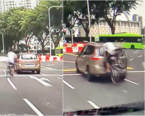 Man cycles in the middle of Newton Circus road, faceplants onto the back of a car