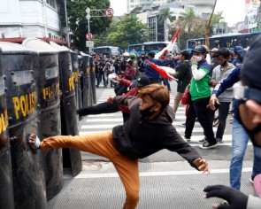Police mistakenly beat undercover cop during jobs law protest in Indonesia