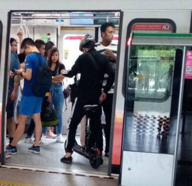 Man sits on PMD in train at Kallang MRT Station