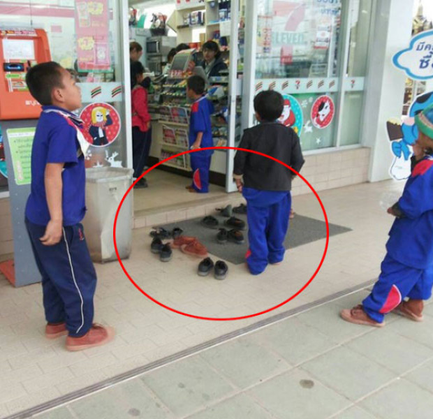 Perfect Asian manners: Polite Thai children remove shoes before entering a 7-Eleven