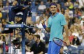 Federer marches on as wild weather, upsets hit US Open