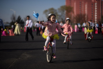 Tiny unicyclists and dancers celebrate North Korea's founder Kim Il Sung
