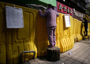 Coronavirus: Shoppers shout over the wall in China's Wuhan