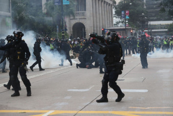 Hong Kong protests: 2 officers attacked, tear gas fired and organiser arrested in rally chaos