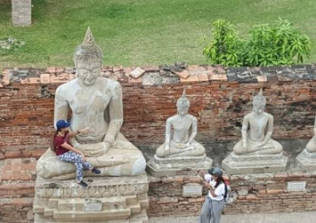Facebook uproar over photo of tourist sitting in Ayutthaya Buddha's lap