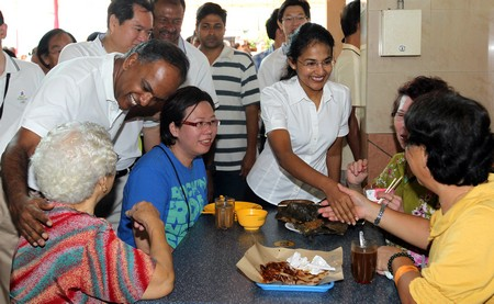 SHANMUGAM (standing, right) and his wife, Mrs Sita SHANMUGAM ...